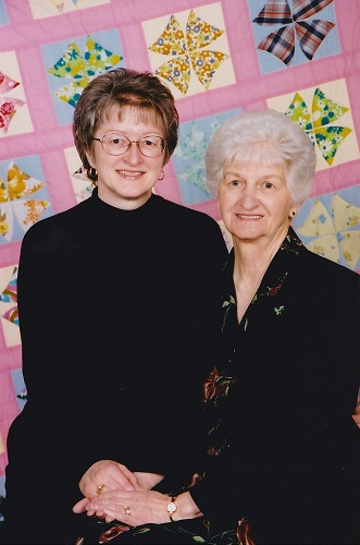 2003 Mom and I with the quilt she made from the remnants of our 1960s home-sewn clothing.